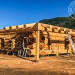 Hip Beam and Rafters on a Wrap Around Porch of this Hand Crafted Western Red Cedar Log Cabin Home under construction at our yard in British Columba for Delivery to Alberta