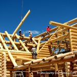 setting a log roof beam on a two Story Custom Handcrafted Log Home for clients in Vermont